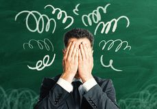 Confused man covering face. Confused businessman covering face on chalkboard background with scribble. Stress concept Stock Image