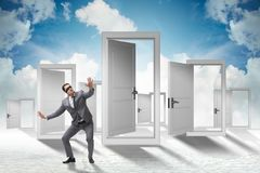 The confused businessman in front of doors. Confused businessman in front of doors Stock Photo
