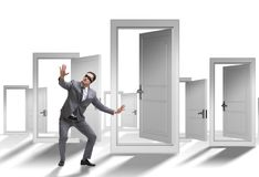 Confused businessman in front of doors stock photo