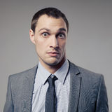 Confused Businessman On Gray Background Royalty Free Stock Photos