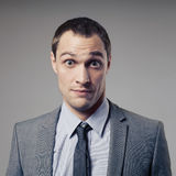 Confused Businessman On Gray Background Stock Photo