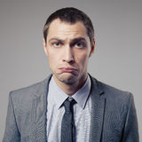 Confused Businessman On Gray Background Royalty Free Stock Image