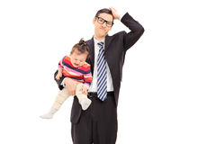Confused businessman holding a crying baby Stock Photo
