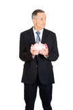 Confused businessman holding piggybank Royalty Free Stock Images
