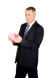 Confused businessman holding piggybank. Confused mature businessman holding piggybank Royalty Free Stock Photos