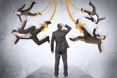Confused businessman looking on hanging people Royalty Free Stock Images