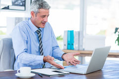 Confused businessman looking at laptop computer. In office Stock Images