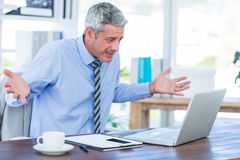 Confused businessman looking at laptop computer. In office Royalty Free Stock Photo