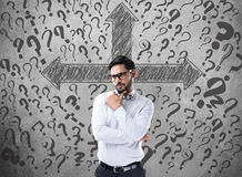 Confused businessman looking for solution. Confused businessman in front of wall with arrow directions and question marks Royalty Free Stock Photography