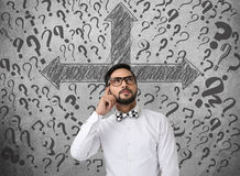 Confused businessman looking for solution. Confused businessman in front of wall with arrow directions and question marks Stock Photos