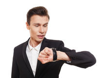 Confused businessman looking at watch Stock Images