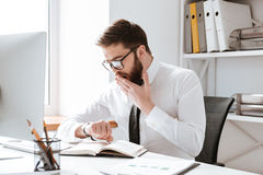 Confused businessman looking at watch. Picture of confused businessman sitting in office while looking at watch Stock Images