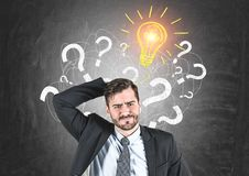 Confused businessman, question marks and idea stock images