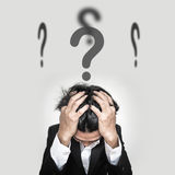 Confused businessman with question marks sign on head stock photography
