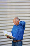 Confused Businessman Reading Binder Against Shutter Royalty Free Stock Images