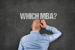Confused Businessman Scratching Head Under MBA Text On Blackboard Stock Image