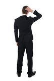 Confused businessman scratching his head. Full length rear view of confused businessman scratching his head over white background Royalty Free Stock Photography