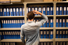 Confused businessman searching for files on cabinet in storage room. Rear view of confused businessman searching for files on cabinet in storage room Royalty Free Stock Photography