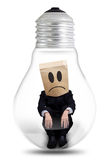 Confused businessman sits inside light bulb Stock Photo