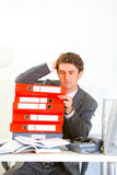 Confused businessman sitting at desk with folders Royalty Free Stock Photo