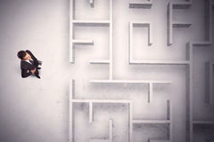 Confused businessman standing at a maze wall. With grungy background Royalty Free Stock Image