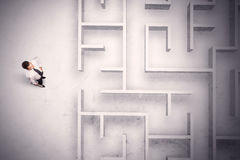 Confused businessman standing at a maze wall. With grungy background Stock Image