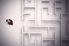 Confused businessman standing at a maze wall. With grungy background Stock Photography