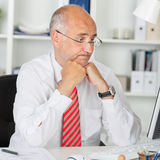 Confused Businessman Staring At Computer At Office Desk. Confused mature businessman staring at computer while leaning on office desk Stock Photography