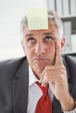 Confused businessman with sticky note on head Royalty Free Stock Photo