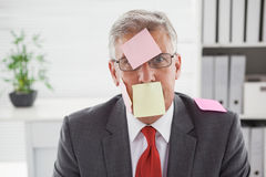 Confused businessman with sticky notes on head Stock Photo