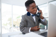 Confused businessman talking on telephone while looking at laptop Royalty Free Stock Images