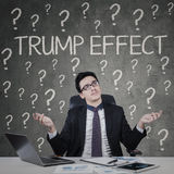 Confused businessman with Trump Effect word. JAKARTA, November 17, 2016: Portrait of a caucasian businessman looks confused with Trump Effect word and question Royalty Free Stock Photos