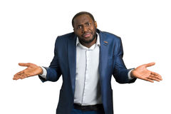 Confused businessman on white background. Unsure afro american manager giving I don t know gesture royalty free stock photography