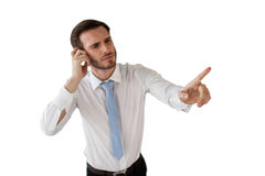 Confused businessman working on invisible interface. Against white background Royalty Free Stock Image