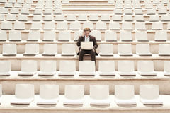 Confused Businessman Working On Laptop In Center Of Empty Audito. Confused middle aged businessman working on laptop while sitting alone in center of empty Royalty Free Stock Photography