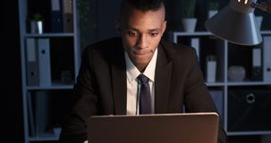 Confused businessman working late night on office laptop. Confused african american businessman working on laptop late in night office stock footage