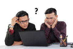 Confused businessmen looking at laptop Royalty Free Stock Image