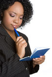 Confused Businesswoman. Confused black businesswoman holding checkbook Royalty Free Stock Image
