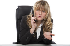 Confused businesswoman asking for clarity. Confused businesswoman frowning as she chats on the telephone at work asking for clarity an a certain point while Stock Photos