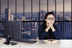 Confused businesswoman with donuts on a plate Royalty Free Stock Photography