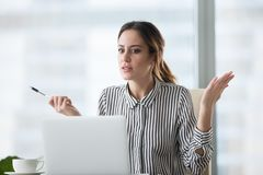 Confused female worker frustrated by laptop crash notice. Confused businesswoman feel at loss looking at laptop screen with error message, frustrated female royalty free stock photo