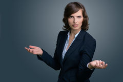Confused Businesswoman with Hands in the Air. Half Body Shot of a Confused Young Businesswoman with Hands in the Air, Looking into the Distance Against Gray Wall Royalty Free Stock Photo