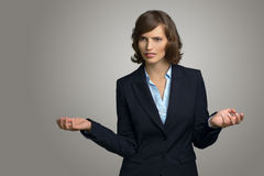 Confused Businesswoman with Hands in the Air. Half Body Shot of a Confused Young Businesswoman with Hands in the Air, Looking into the Distance Against Gray Wall Royalty Free Stock Photography