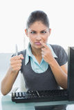 Confused businesswoman with pen at office desk Stock Image