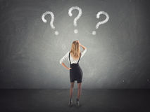 Confused businesswoman thinking, looking at questions mark in the wall. Confused businesswoman thinking, looking at questions mark stock photo