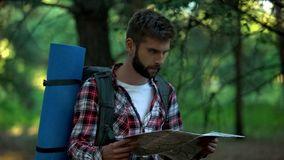 Confused camper orienteering with map in forest, searching for right way. Stock photo stock photo
