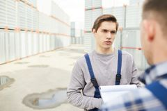 Confused cargo worker talking to colleague royalty free stock images