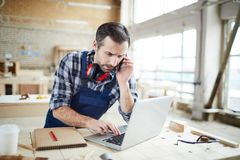 Confused carpenter checking information while talking by phone royalty free stock images