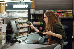 Confused cashier woman on workspace in supermarket. Side view picture of confused cashier woman on workspace in supermarket shop. Looking aside Stock Photography