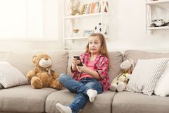 Confused casual little girl watching tv while sitting on sofa at home. Confused little casual girl watching tv at home. Female kid sitting on sofa with her toy Stock Photos